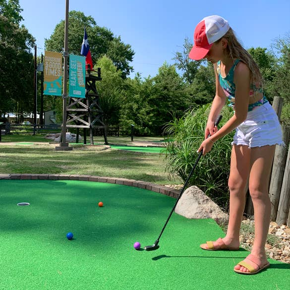 A caucasian girl stands with her putter on a mini golf course.