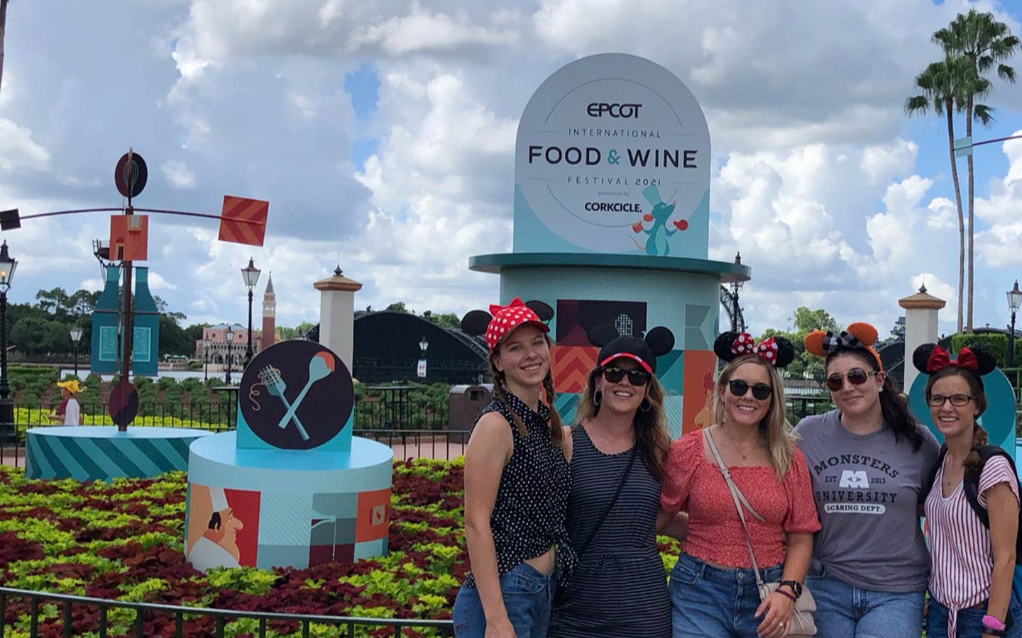 Five caucasian women wearing Mickey and Minnie ears stand in front of a display for the Epcot International Food & Wine Festival near the World Showcase Lagoon.