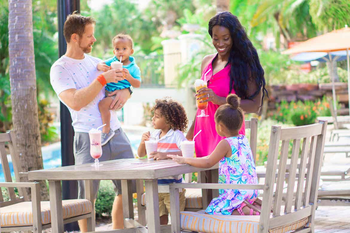 Featured Contributor, Sally Butan (back-right) and her family of five enjoy some beverages at a table near the lazy river at our Orange Lake resort located near Orlando, FL.