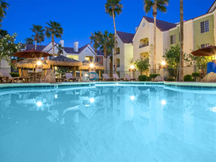 Pool surrounded by palm trees at Desert Club Resort.