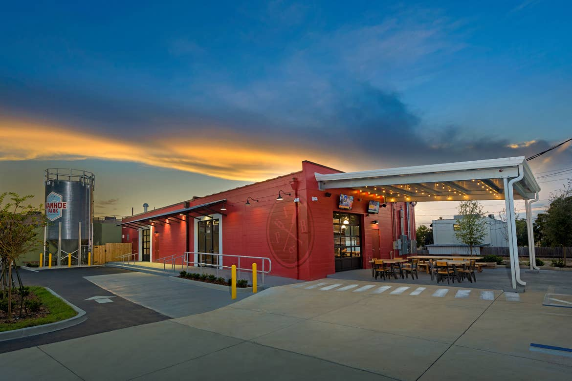A multicolored cinderblock building exterior with fermenter decal that reads, 'Ivanhoe Park Brewing Co.' as the sun sets in the distance.