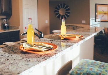 Kitchen bar with two stools and table settings in a villa in North Village at Orange Lake Resort near Orlando, Florida
