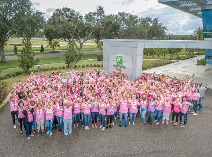 Large group of people all waring pink and making heart shapes with their hands towards the camera and Holiday Inn Club Vacation's corporate headquarters.