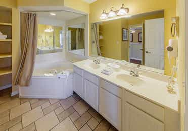 Bathroom with two sinks, large mirror, and shower/tub combination in a presidential two bedroom villa at Piney Shores Resort in Conroe, Texas
