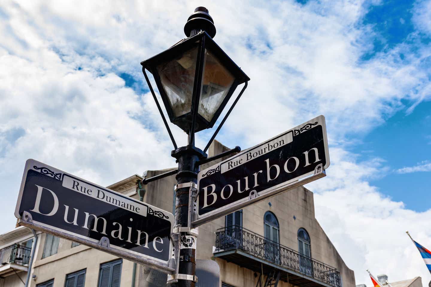 A black lamppost indicating the streets of 'Dumaine' (left) and 'Bourbon' (right) under a cloudy blue sky.