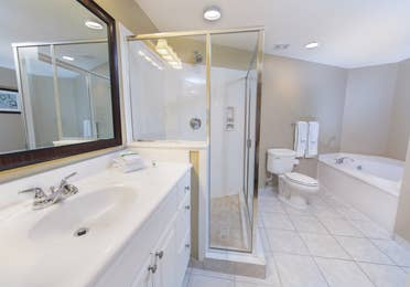 Master bathroom with whirlpool tub, walk in shower, toilet and sink with large mirror in a two-bedroom villa at Galveston Beach Resort