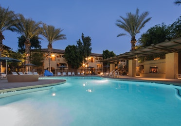 Lighted swimming pool surrounded my palm trees at night at Scottsdale Resort in Arizona