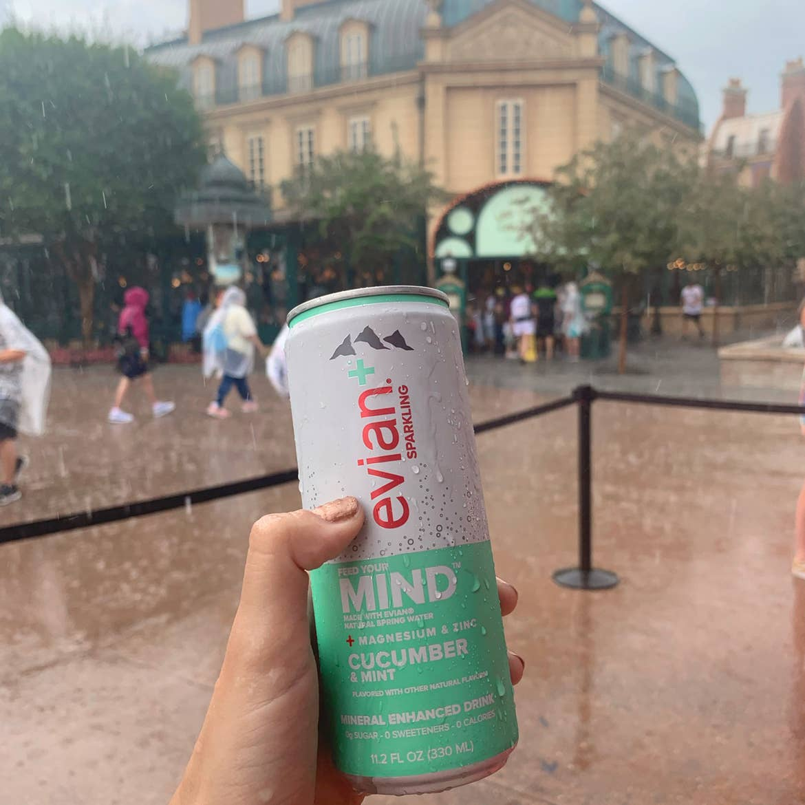A hand holds an aluminum can of Evian near the France Pavilion at Epcot in the rain.
