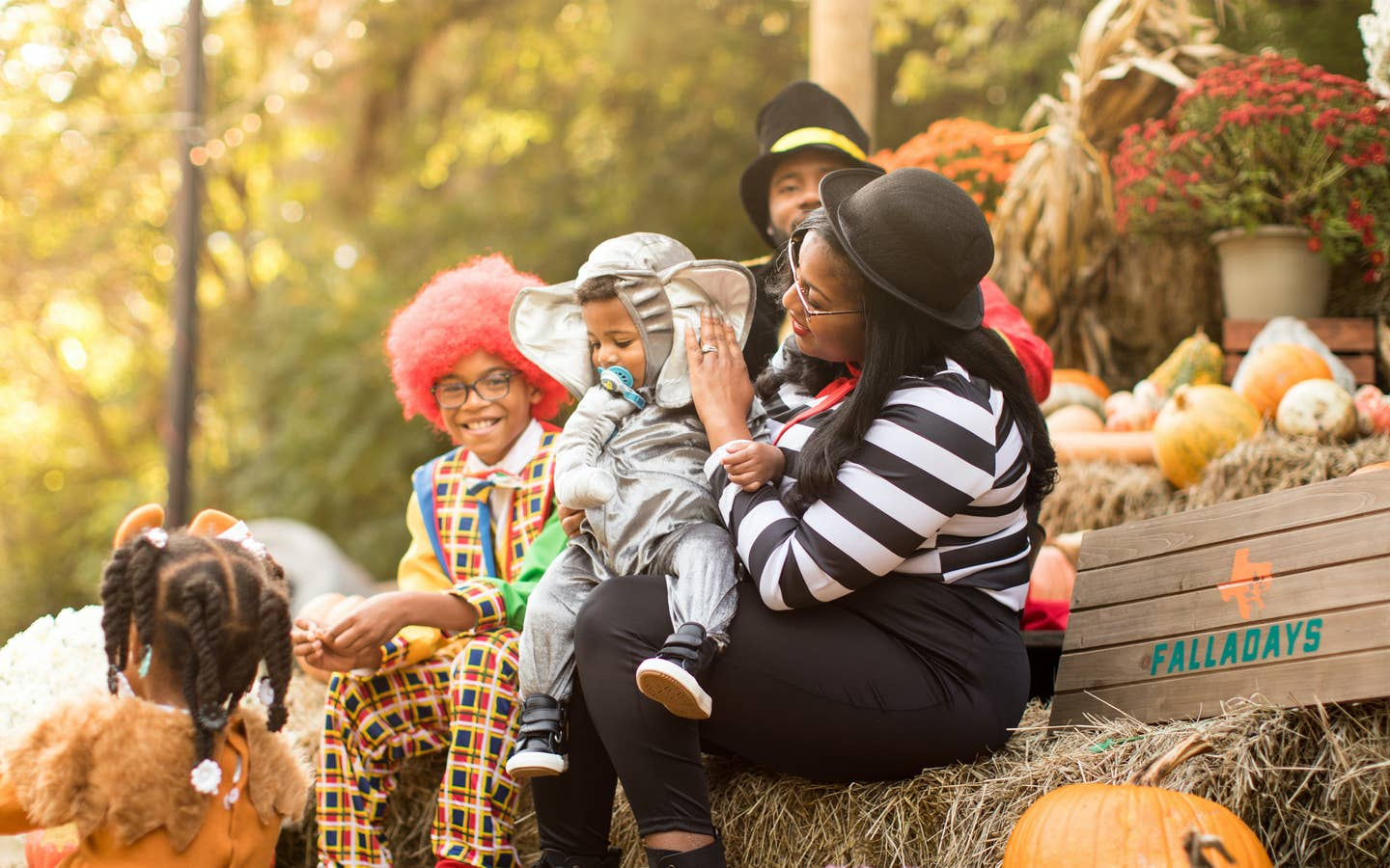 Family in costumes sitting on a pumpkin patch at the Villages Resort in Flint, TX.