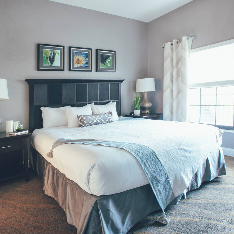 Bedroom with large window and two night stands in a one bedroom villa in North Village at Orange Lake Resort near Orlando, Florida