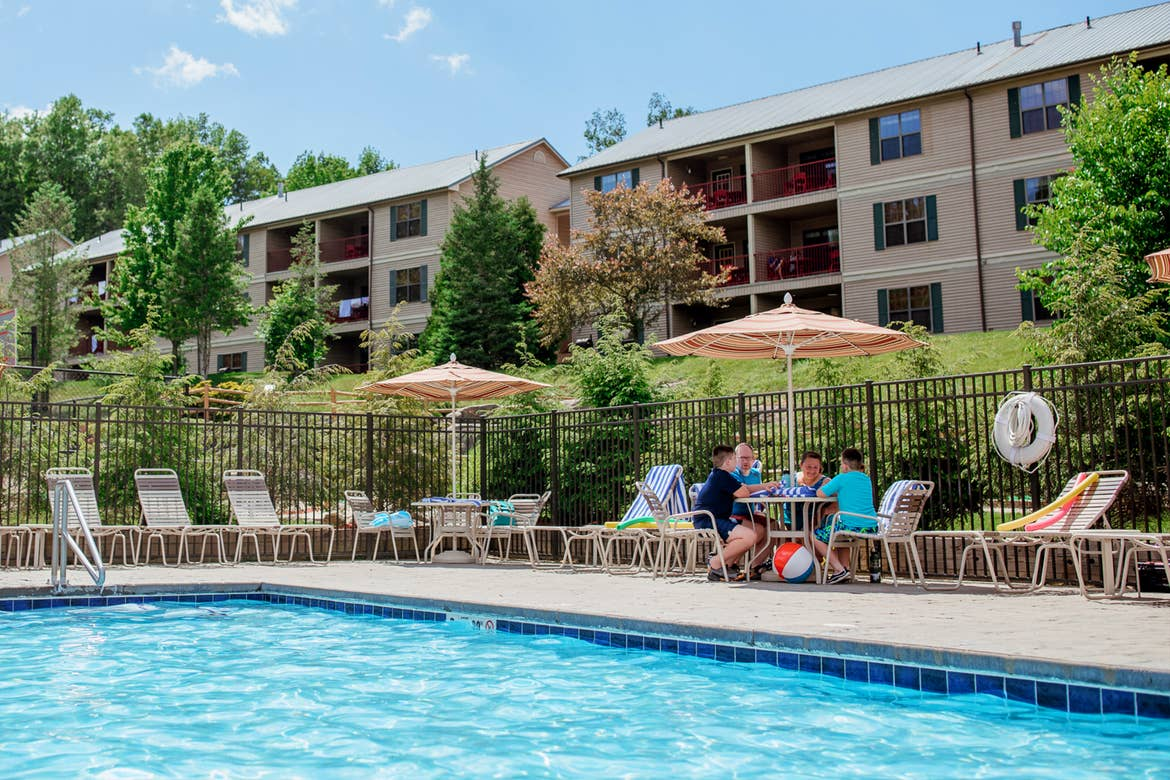 A caucasian family of five (left to right: Two tween boys, a young girl, a woman and man) sit at a table under an umbrella near an outdoor pool surrounded by green trees and the exteriors of our Oak and Spruce resort located in Lee, Massachusetts.