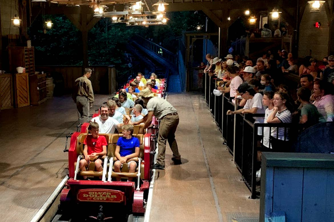 Multiple riders load onto a roller coaster vehicle at Silver Dollar City.