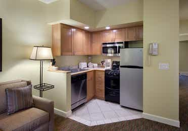 Kitchenette with stainless steel fridge, microwave, dishwasher, sink, and small oven in a one-bedroom villa at Lake Geneva Resort