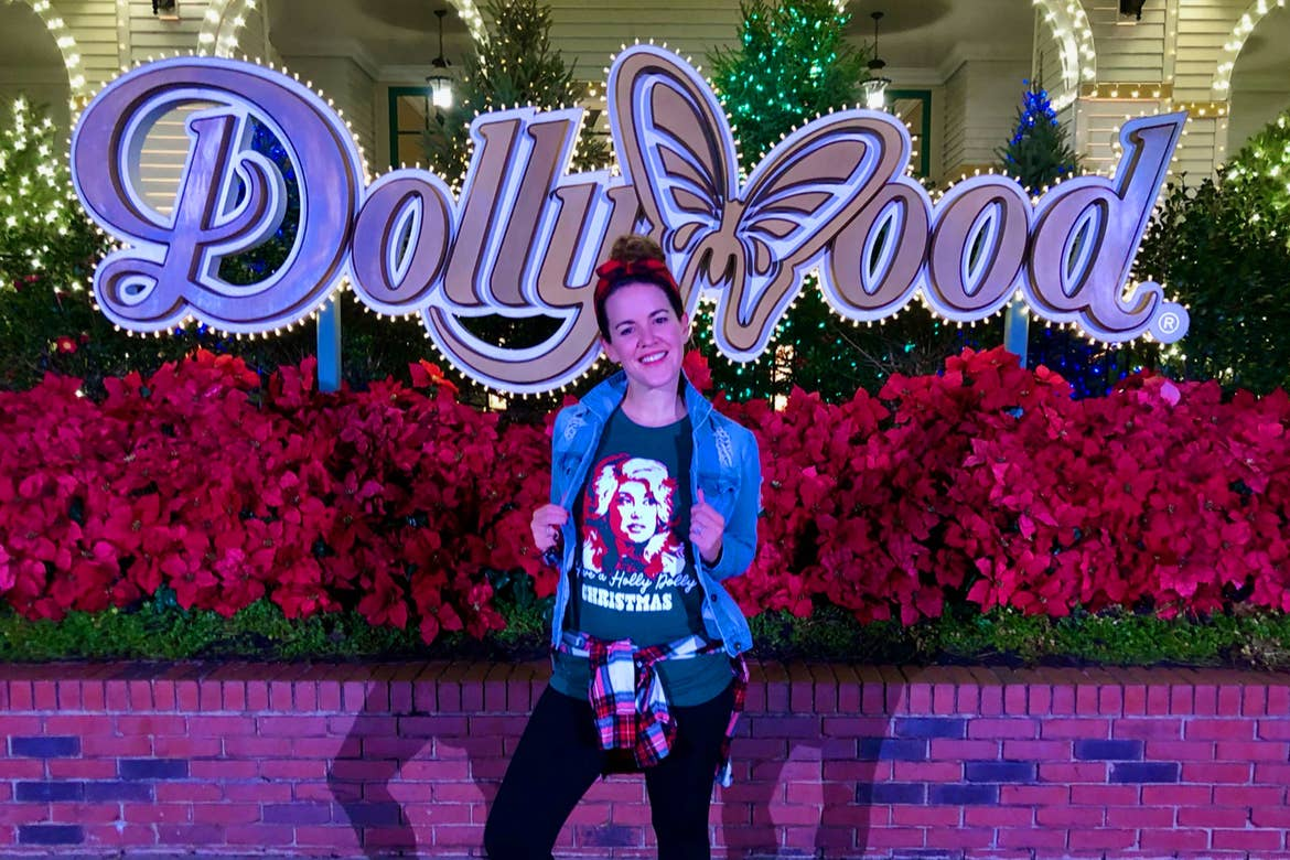 Featured Contributor, Jennifer C. Harmon, sports a Dolly-inspired shirt in front of the Dollywood marquee at 'Dollywood.'