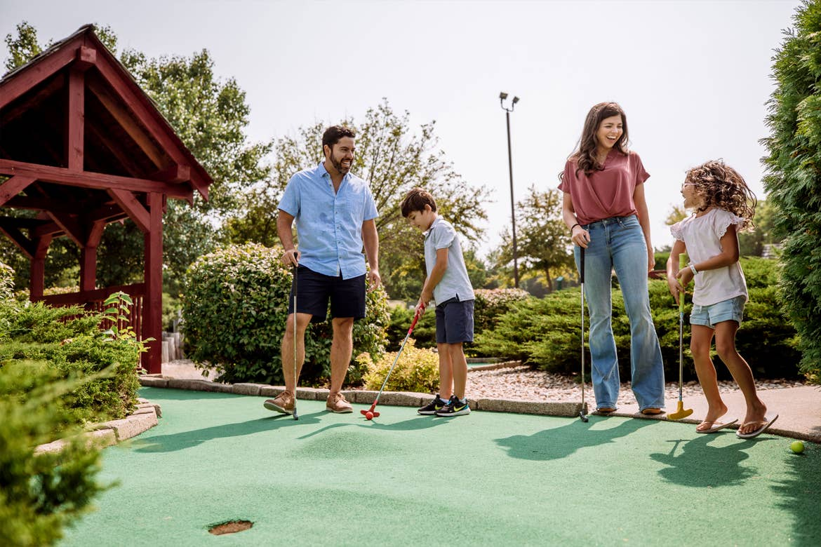 from left to right: A man, a young boy, a woman and a young girl play mini golf outdoors.