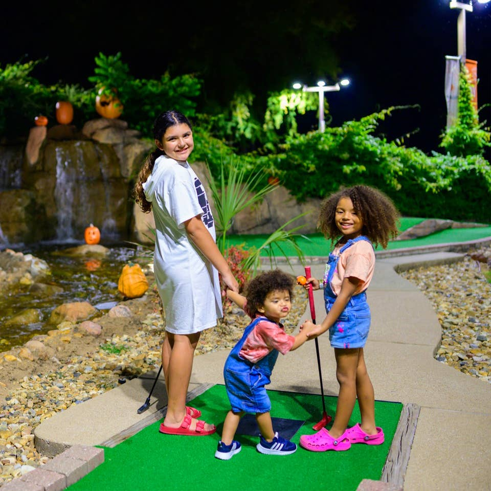 A tween girl (left), a young girl (right) and toddler (middle) stand on a mini golf course holding putters at night.