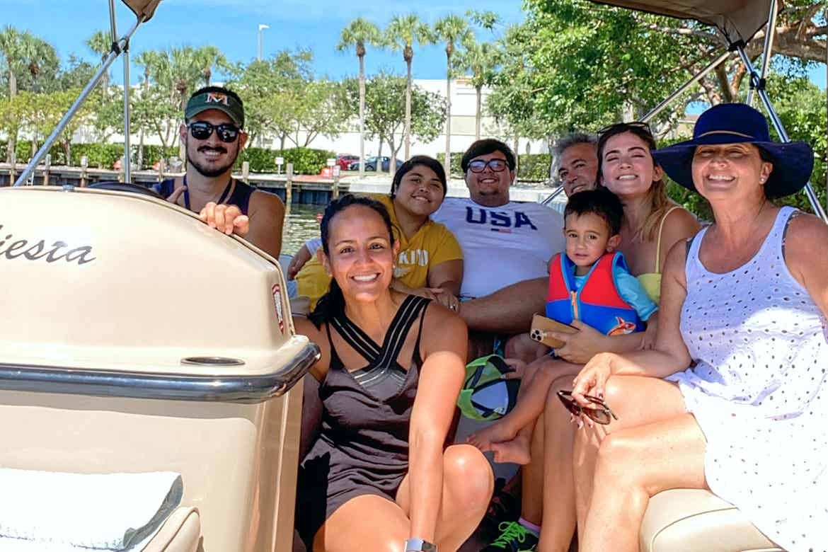 Featured Contributor, Danny Pitaluga (left) wears sunglasses, a blue tank and a hat behind the steering wheel while his wife and their extended family sit on a boat.