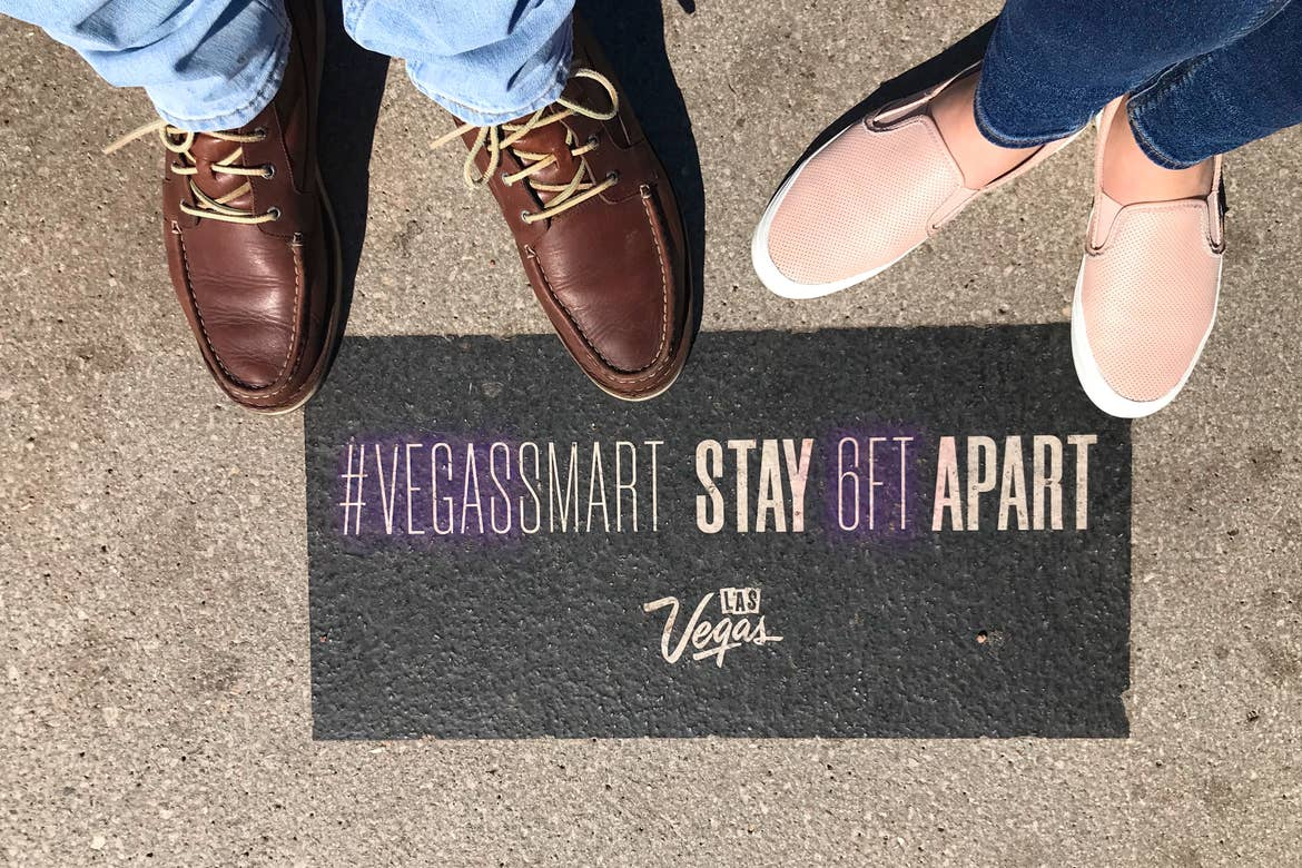 Featured Contributor, Ashley Fraboni (right) and her fiancé (left) stand on a marker that indicates social distancing that reads, '#VegasSmart Stay 6 FT. Apart.'