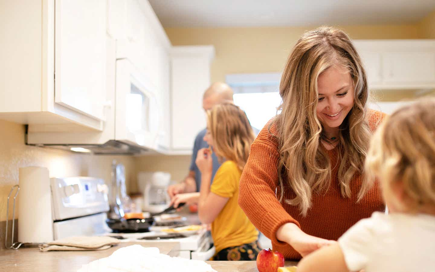 A woman in an orange sweater (front-right) helps serve a meal her husband and daughter (back-left) prepared in their Villa kitchen.