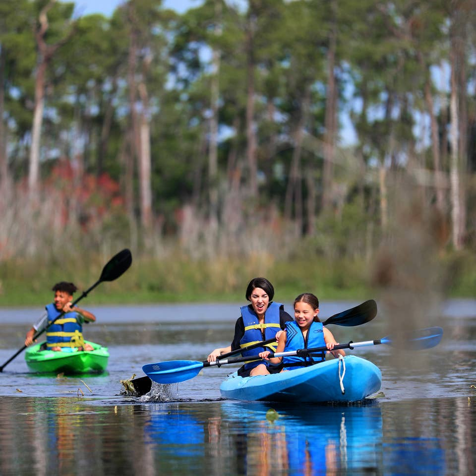 Featured Contributor, Clarissa Laskey (middle), kayaks with her daughter (right) in a blue kayak while her son (left) kayaks in his own green kayak.
