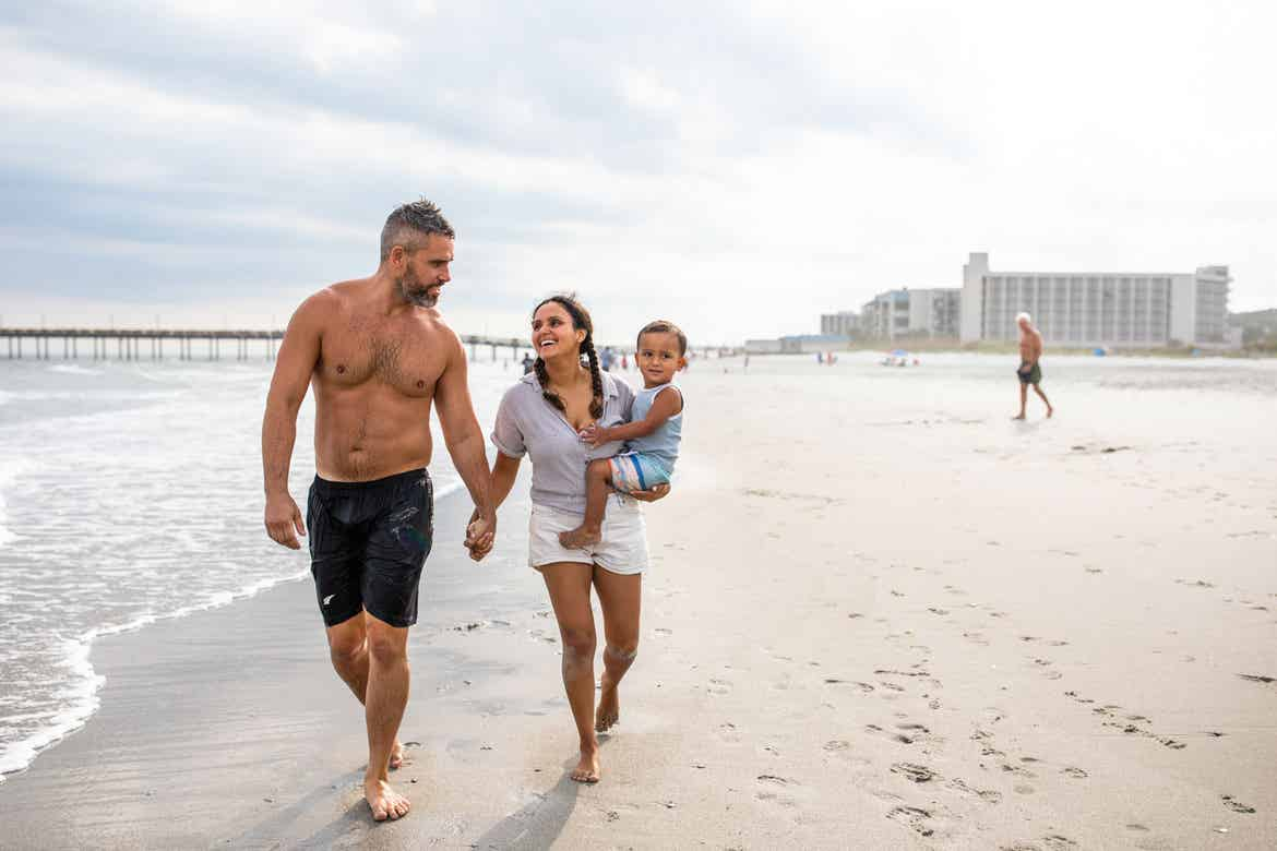Author, Brenda Rivera Stearns (right), and husband, Isaiah (left), walk along the sandy beach while toting her son.