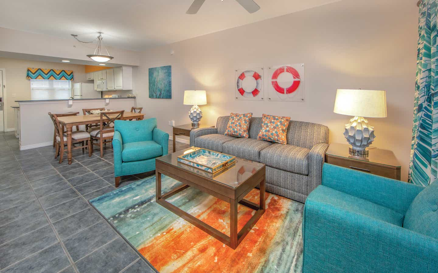 Living room with couch, two accent chairs, and coastal decor in a one-bedroom villa at Panama City Beach Resort