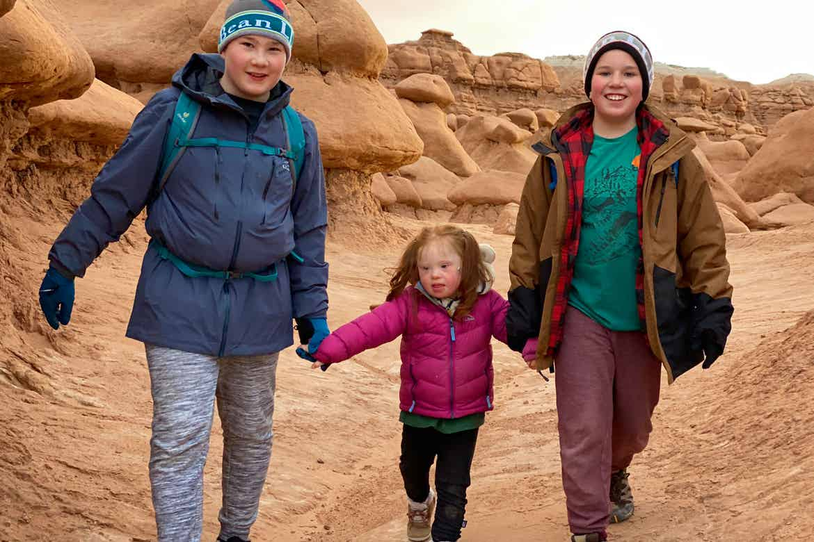 Featured Contributor, Melody Forsyth's two sons (left and right) walk with daughter, Ruby (middle) in front of a rock formation holding hands while wearing hiking backpacks.