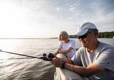 Two adults fishing off of a pontoon boat at Villages Resort in Flint, Texas.