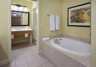 Bathroom with tub and sink with large mirror in a one-bedroom villa at Lake Geneva Resort