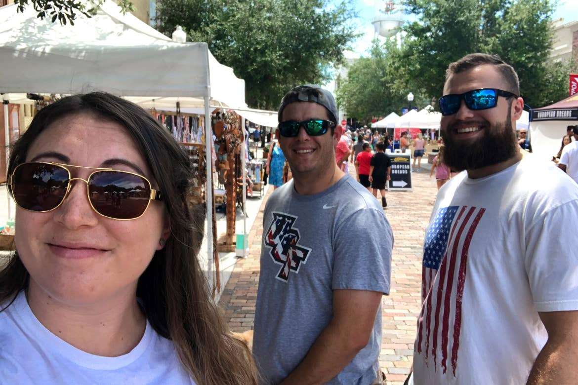 A caucasian woman (left) wearing a white t-shirt and sunglasses stands in front of two caucasian men (right) wearing t-shirts and sunglasses in front of the Winter Garden Famers Market.
