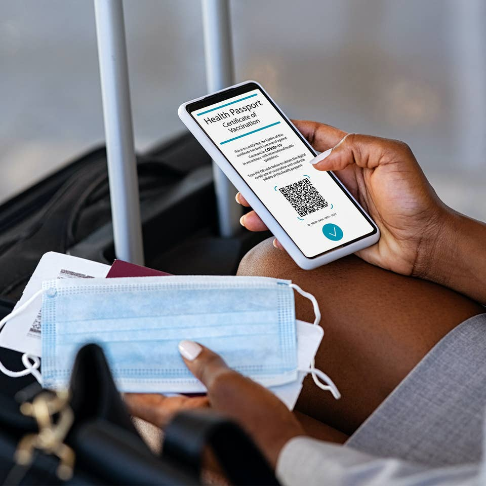 Traveler pulling out their cell phone to look at their digital health pass/vaccine passport, with a mask in their hand and luggage in front of them.