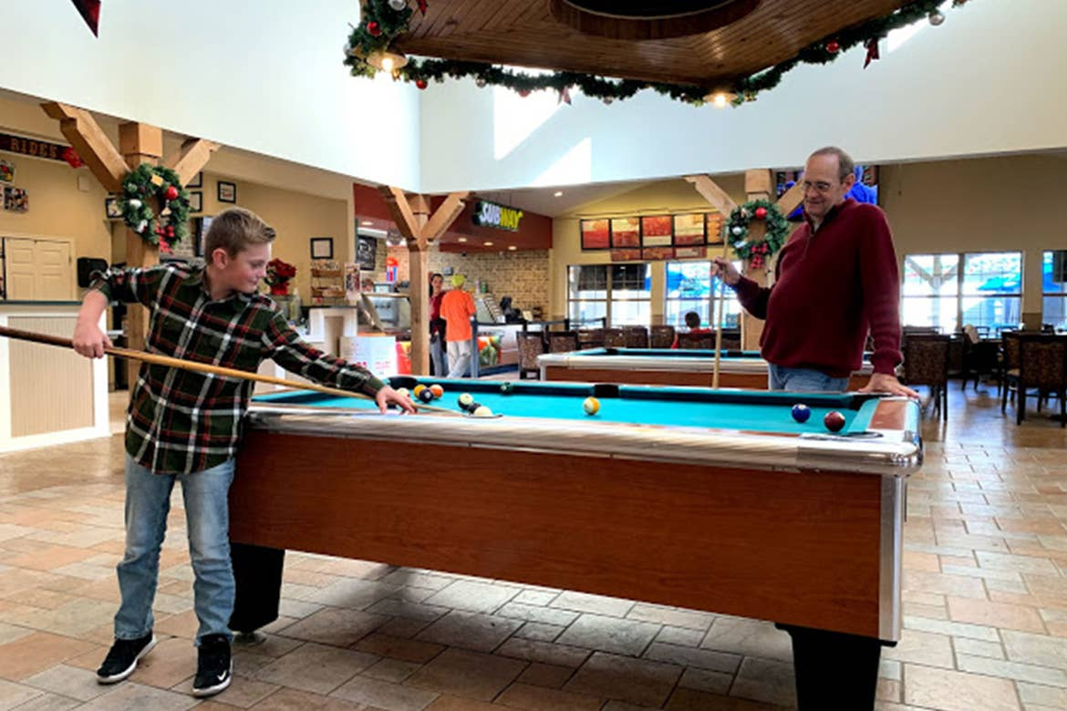 Amanda Nall's father (right) watches her son (left) play pool in the game room at the Villages Resort.