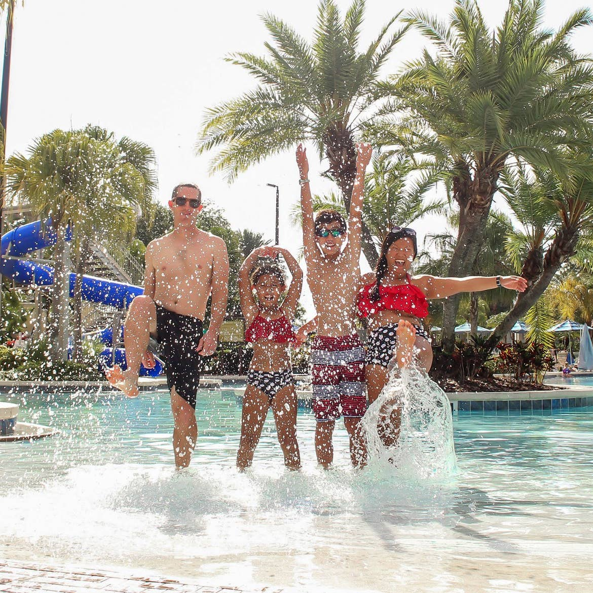 A biracial family of four wear black, red and white swimsuits while splashing in the zero-entry pool at our Orange Lake Resort located in Orlando, Florida.