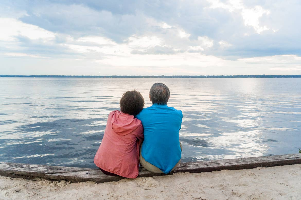 An older Asian woman (left) wears a pink zip-up hoodie next to an older Asian man (right) wearing a blue polo and khaki shorts as they sit on a beach dipping their toes into the water.