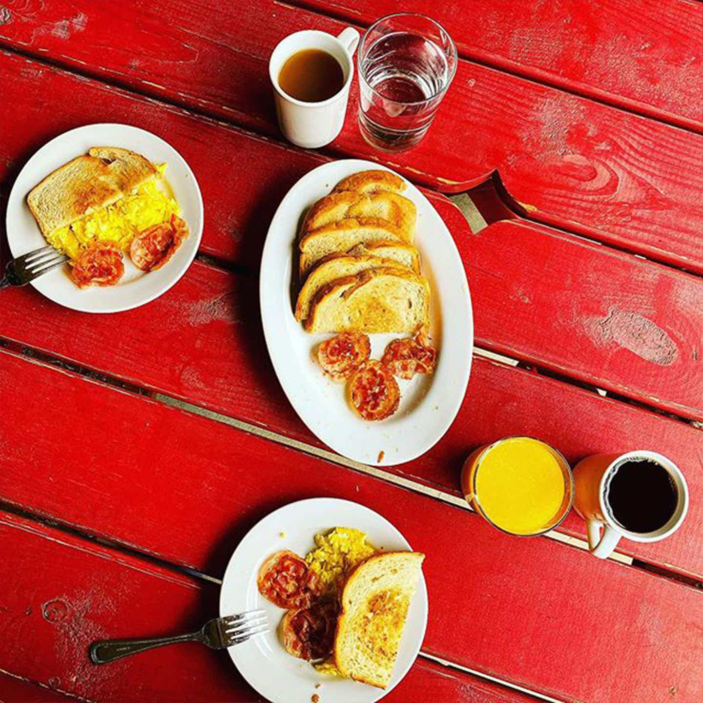 Three plates of egg and toast with beverages are placed on a red picnic table.