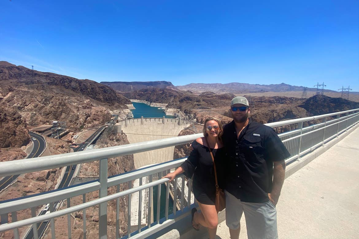 A caucasian woman wearing sunglasses (left) poses near a caucasian man wearing sunglasses and a hat (right) in front of the Hoover Damn under a clear blue sky.