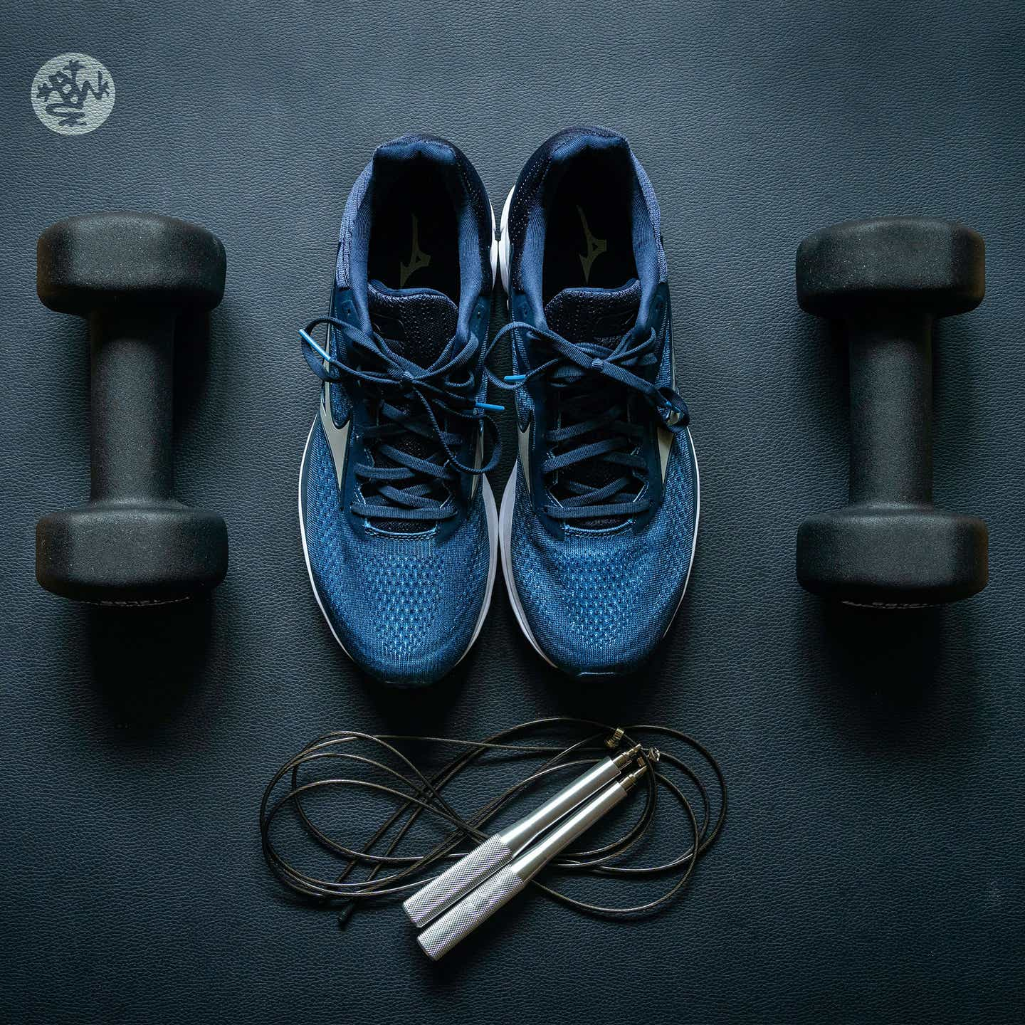 A pair of blue gym shoes, two black free weights, and a jump rope lay out over a navy yoga mat.