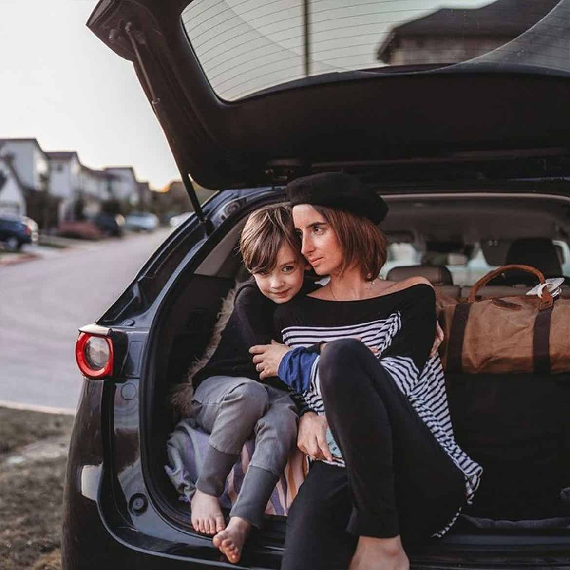 Featured Contributor, Eileen Lamb's son sits alongside her in the trunk of their black car surrounded by suitcases.