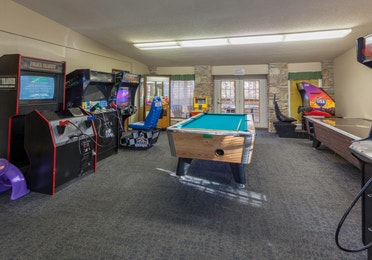 Game room with a pool table, air hockey table, and arcade games at Ozark Mountain Resort in Kimberling City, Missouri