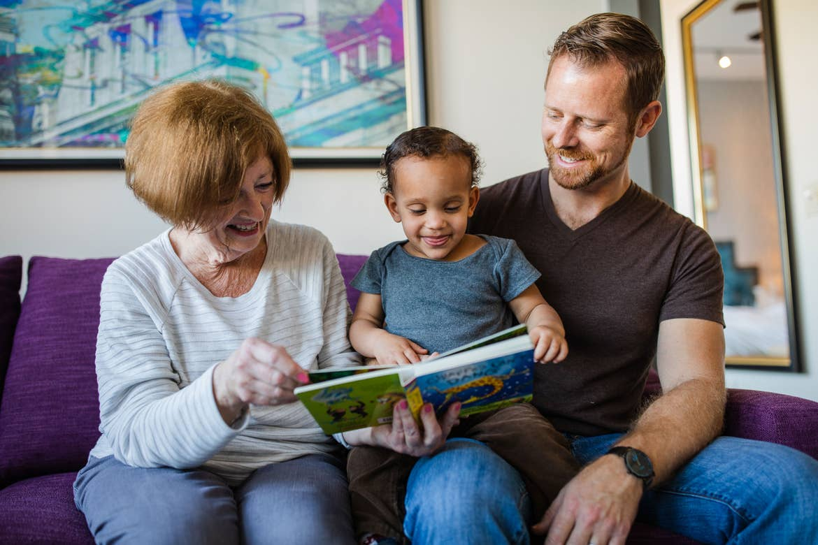 Featured Contributor, Sally Butan of @butanclan's husband (right) sits on a purple couch with his mother (left) as they read to his son (middle) at our Signature Collection villa in our resort in New Orleans, Louisiana.