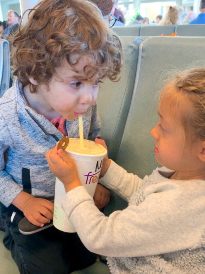 Raff's two kids drinking juice and eating snacks at the airport