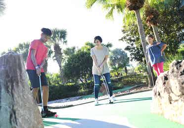 Family playing mini golf at Cape Canaveral Beach Resort.