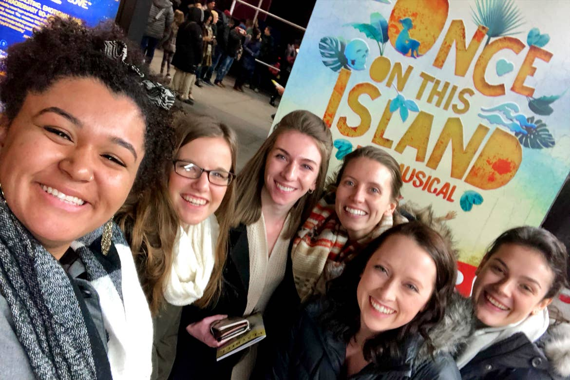 Several women stand wearing scarves and winter coats in front of a sign that reads, 'Once On This Island - A Musical' in New York City.