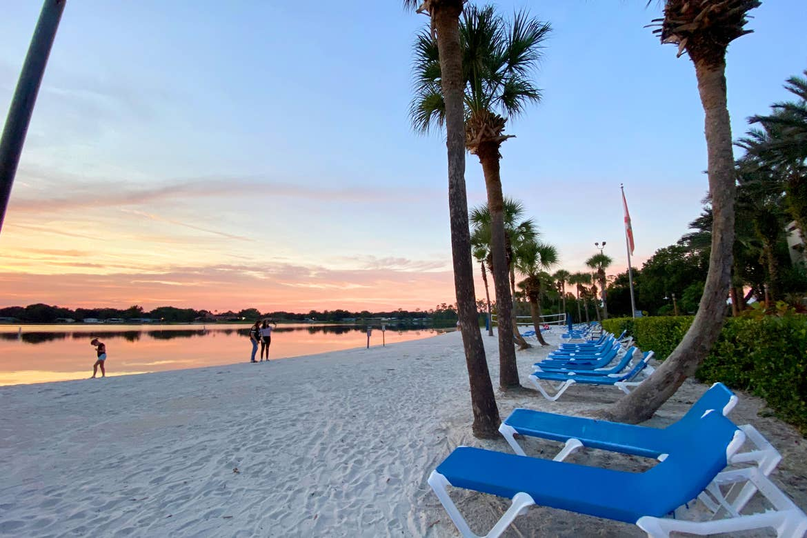 Blue beach chairs and guests pose at the sunset near the sands at our Orange Lake resort in Orlando, Florida.