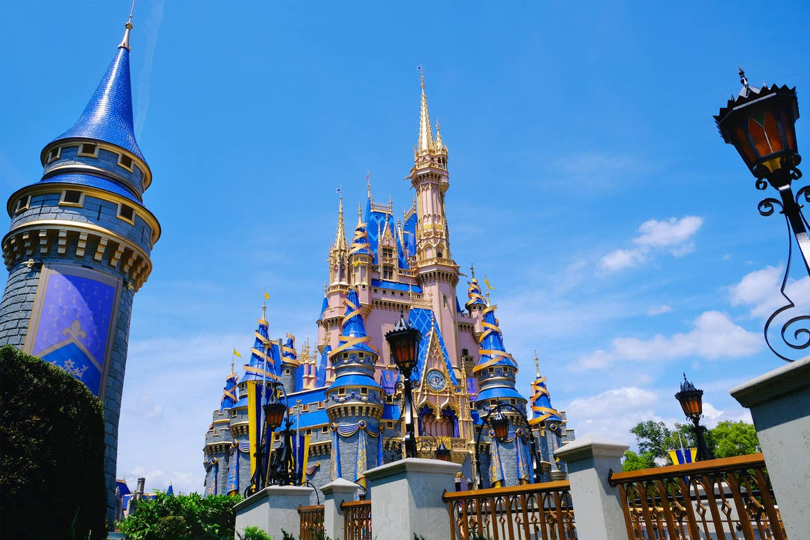 Cinderella's Castle at Magic Kingdom in Walt Disney World Resort is decorated in gold and blue ribbons for its upcoming 50th Anniversary.