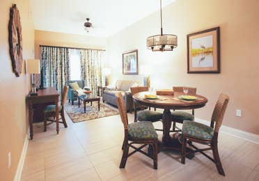 View of dining table and living room in a one bedroom villa in North Village at Orange Lake Resort near Orlando, Florida