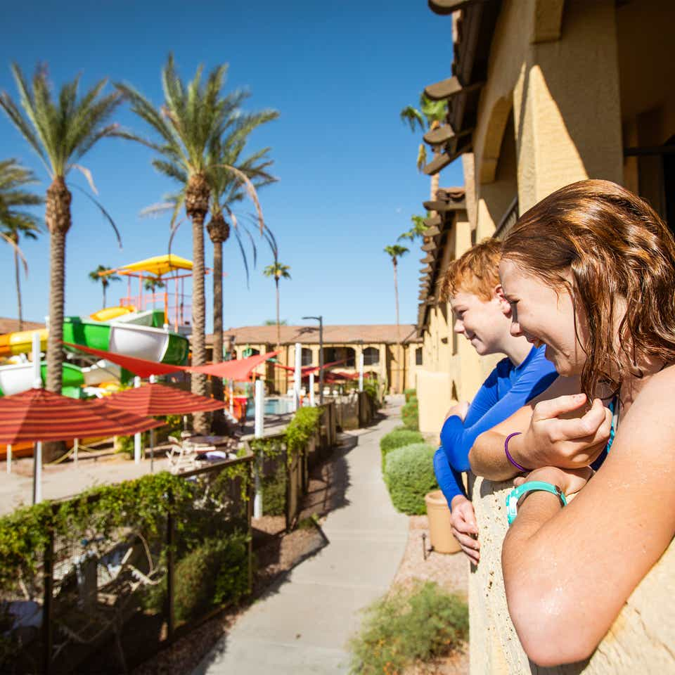 Two kids looking at outdoor pool from their villa balcony at Scottsdale Resort.
