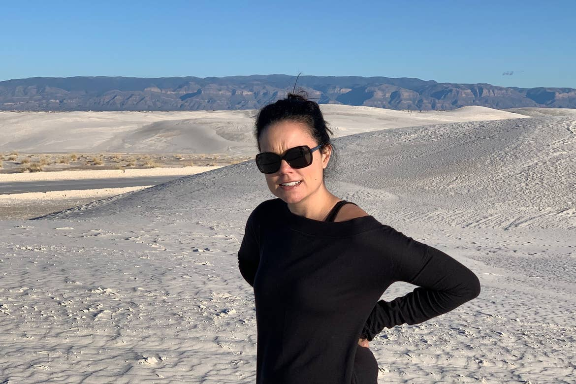 Author, Lauren Layne, stands looking frustrated at the White Sands National Monument.