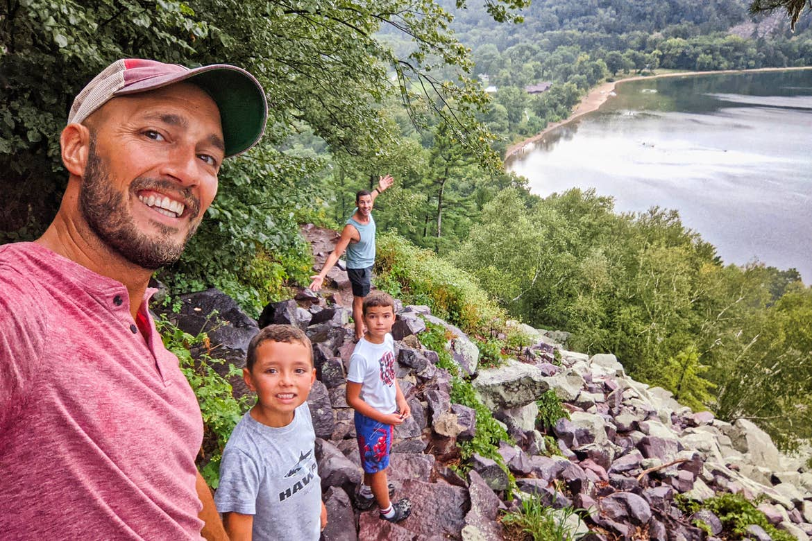 A family of two men and two boys overlook a river from a cliff.