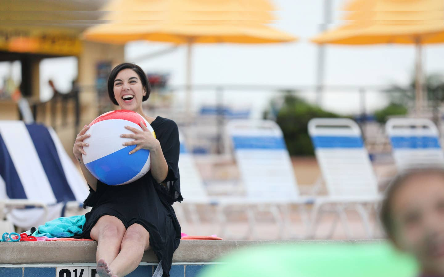 Woman holding beach ball while sitting poolside.